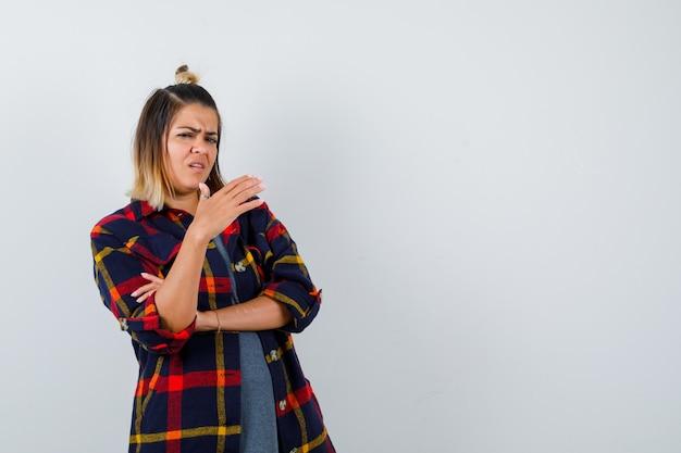 Giovane donna in camicia casual a quadri alzando la mano davanti a lei e guardando scontento, vista frontale.