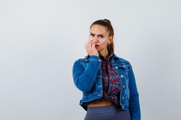Giovane donna in camicia a scacchi, giacca di jeans che si morde le unghie e sembra pensierosa, vista frontale.