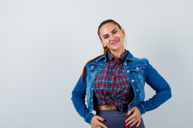 Giovane donna in camicia a scacchi, giacca di jeans in posa mentre sembra gioiosa, vista frontale.
