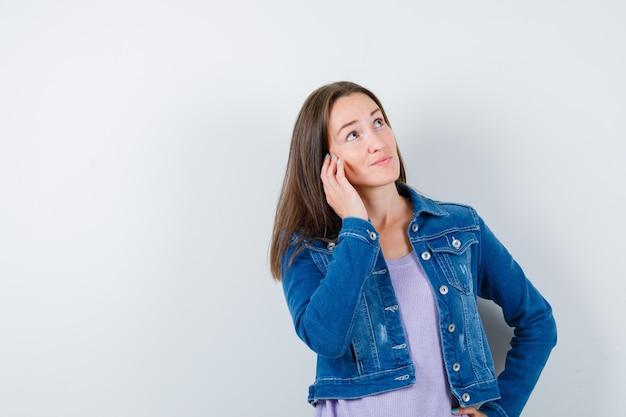 Giovane donna che controlla la pelle del viso sulla guancia mentre alza lo sguardo in maglietta, giacca e sembra pensierosa. vista frontale.