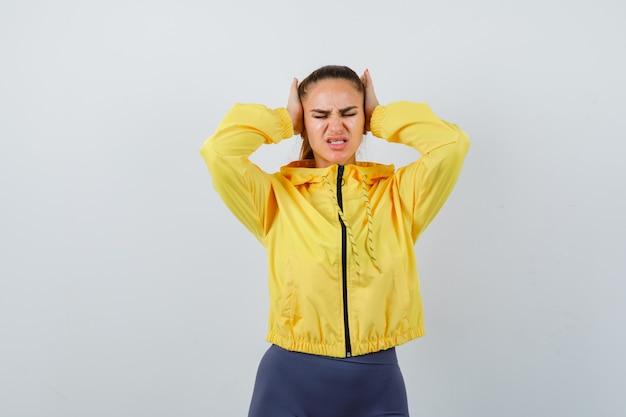 Giovane donna che stringe la testa con le mani in giacca gialla e sembra stressata, vista frontale.