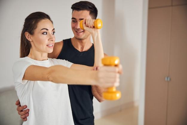 Giovane donna che fa esercizi fisici con manubri
