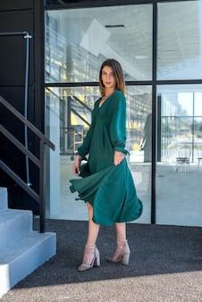Giovane donna alla moda vestito verde posign vicino edificio di vetro, stile di vita estivo