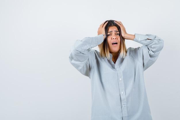Giovane donna che si tiene per mano sulla testa in camicia oversize e sembra addolorata. vista frontale.