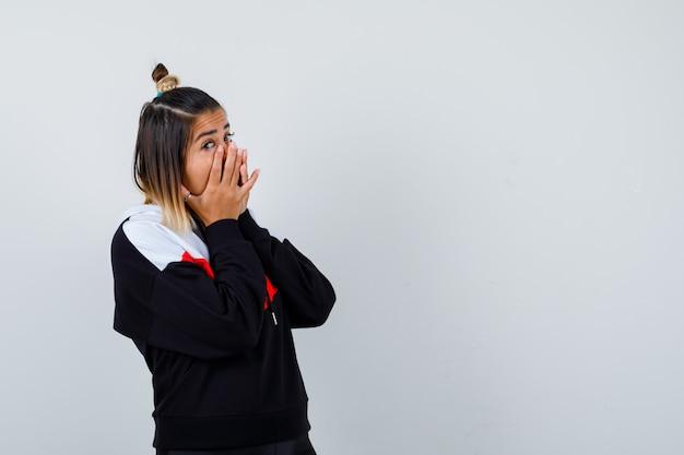 Giovane donna che si tiene per mano sulla bocca in felpa con cappuccio e sembra imbarazzata.