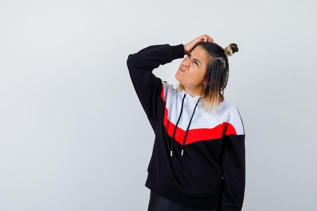 Giovane donna in felpa con cappuccio che si gratta la testa mentre guarda da parte e sembra pensierosa