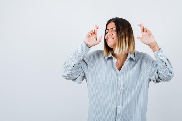 Giovane donna che tiene le dita incrociate in una camicia oversize e sembra felice. vista frontale.