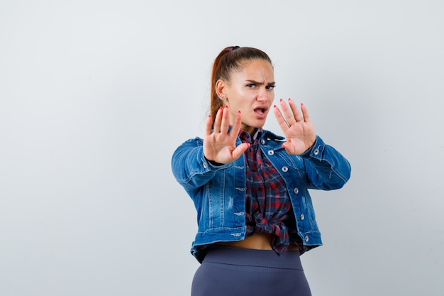 Giovane donna che tiene le mani per difendersi in camicia a scacchi, giacca di jeans e sembra ansiosa. vista frontale.