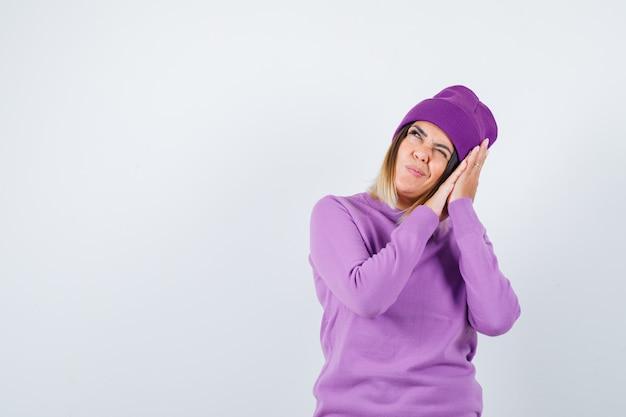 Giovane donna che si appoggia sulle mani come cuscino in maglione viola, berretto e sembra gioiosa. vista frontale.