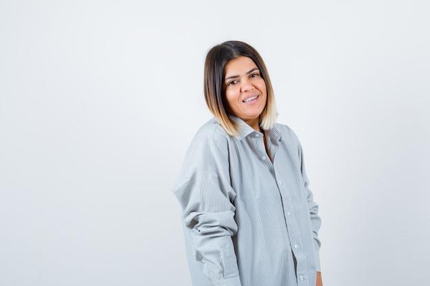 Giovane donna che guarda l'obbiettivo in camicia oversize e guardando allegro, vista frontale.