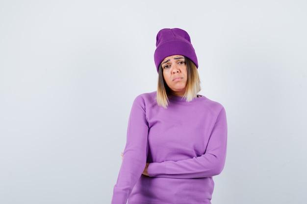 Giovane donna che guarda l'obbiettivo mentre il viso accigliato in maglione viola, berretto e guardando deluso. vista frontale.