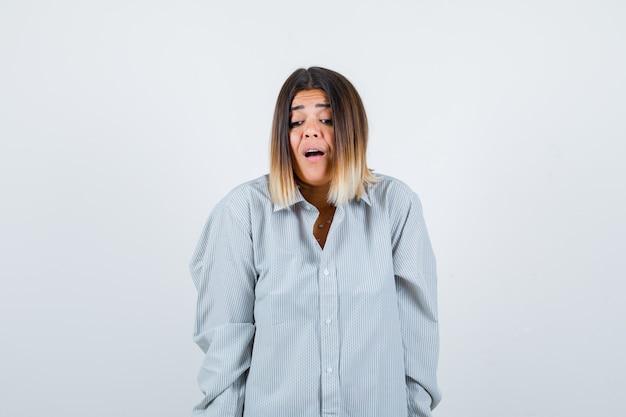 Giovane donna che guarda in basso in camicia oversize e sembra perplessa. vista frontale.