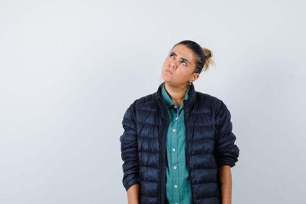 Giovane donna alzando lo sguardo in camicia, piumino e guardando premuroso, vista frontale.