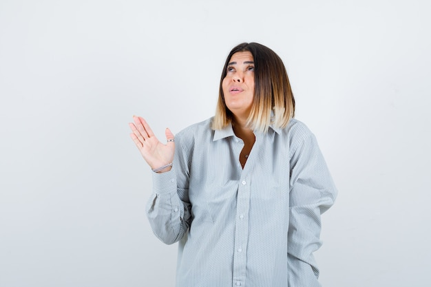 Giovane donna che guarda in alto mentre allarga il palmo in una camicia oversize e sembra premurosa, vista frontale.