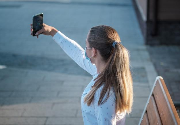 Una giovane donna con una mascherina medica si fa un selfie con il suo smartphone. modalità maschera durante la pandemia covid-19