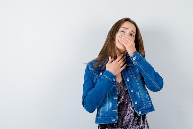 Giovane donna che pizzica il naso a causa del cattivo odore in camicetta, giacca di jeans e sembra disgustata, vista frontale.