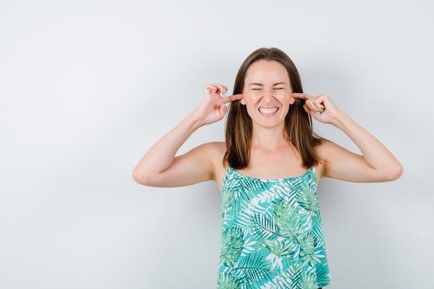 Giovane signora che tappa le orecchie con le dita e sembra annoiata. vista frontale.