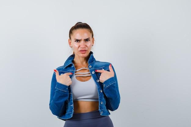 Giovane donna che indica se stessa mentre fa una domanda in alto, giacca di jeans e sembra seria, vista frontale.