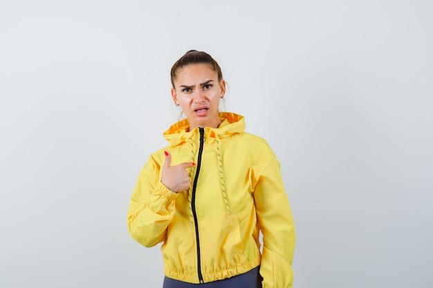 Giovane donna che indica se stessa mentre fa una domanda in giacca gialla e sembra seria, vista frontale.