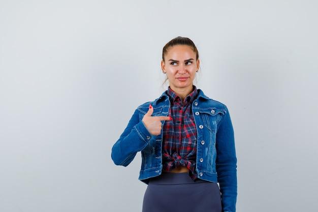 Giovane donna che indica se stessa in camicia a scacchi, giacca di jeans e sembra soddisfatta. vista frontale.
