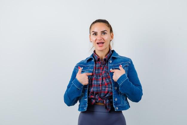 Giovane donna che indica se stessa in camicia, giacca e sembra scioccata, vista frontale.