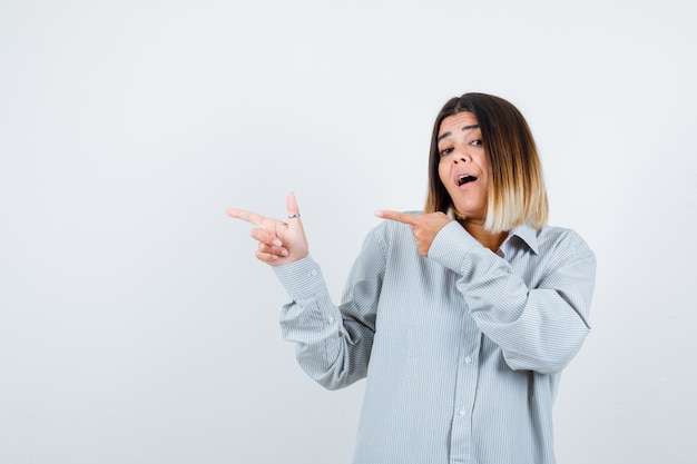 Giovane donna che indica il lato sinistro in una camicia oversize e sembra perplessa. vista frontale.