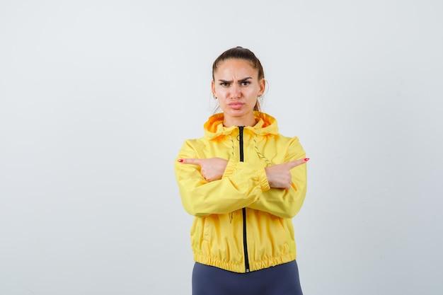 Giovane donna che punta a destra e a sinistra in tuta da ginnastica e sembra triste, vista frontale.