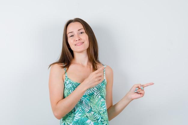 Giovane donna che indica il lato destro in camicetta e sembra felice. vista frontale.