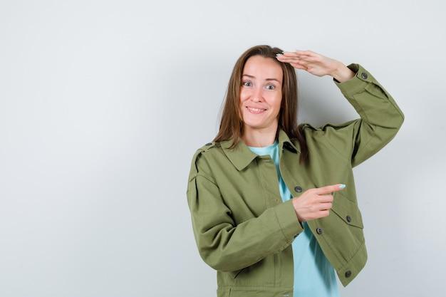 Giovane donna che indica il lato destro mentre con la mano sulla testa per vedere chiaramente in t-shirt, giacca e sembra felice, vista frontale.