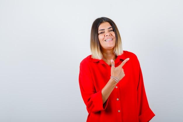 Giovane donna che punta nell'angolo in alto a destra con una maglietta rossa oversize e sembra felice, vista frontale.