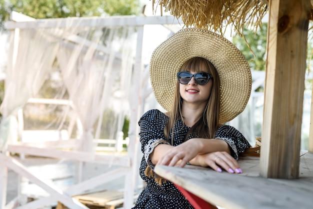 Giovane signora che posa all'ora legale vicino al lago al gazebo bianco