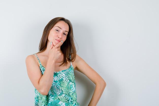 Giovane donna in posa tenendo la mano sul fianco in camicetta e guardando fiducioso, vista frontale.