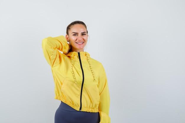 Giovane donna in posa mentre con la mano dietro il collo in giacca gialla e guardando gioiosa, vista frontale.