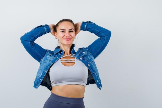 Giovane donna in posa mentre con le mani dietro la testa in alto, giacca di jeans e dall'aspetto attraente. vista frontale.