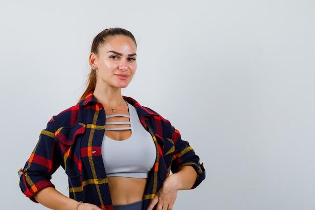 Giovane donna in posa con le mani sulla vita in alto, camicia a quadri e dall'aspetto attraente. vista frontale.