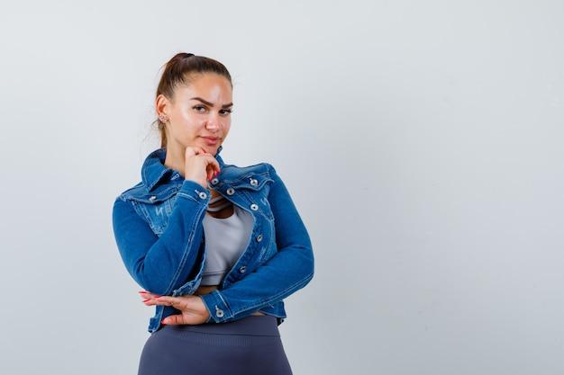 Giovane donna che sostiene il mento in mano in alto, giacca di jeans e sembra sicura, vista frontale.