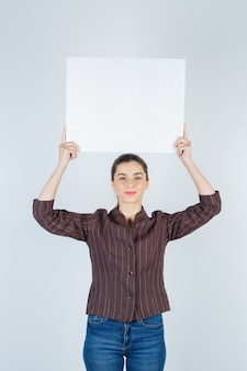 Giovane donna che alza un poster di carta in camicia, jeans e sembra soddisfatta, vista frontale.