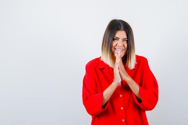 Giovane donna in camicia rossa oversize che prega con le mani insieme chiedendo perdono e sembra felice, vista frontale.