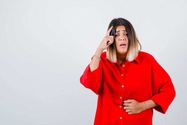 Giovane donna in camicia rossa oversize che soffre di mal di stomaco, tiene il dito sulla testa e sembra dolorosa, vista frontale.
