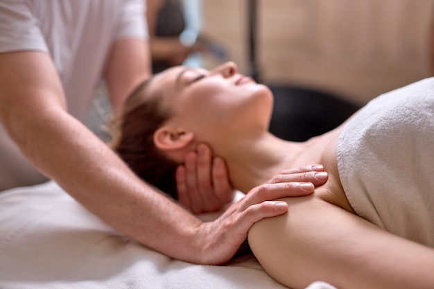 La giovane signora si rilassa durante il massaggio della stazione termale nel centro di bellezza