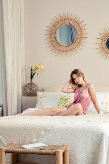 Giovane signora che si rilassa nella camera da letto a casa