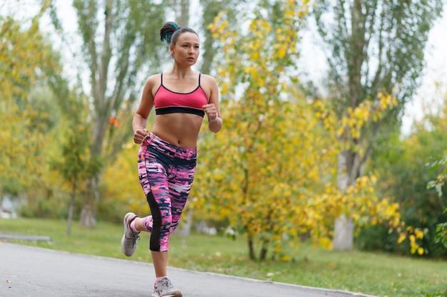 Giovane donna che corre. corridore della donna che attraversa la strada del parco di primavera. allenamento in un parco.