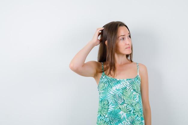 Giovane donna che si gratta la testa mentre guarda lontano e sembra pensierosa, vista frontale.