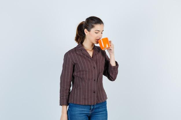 Giovane donna in camicia, jeans che beve dalla tazza e guarda premurosa, vista frontale.