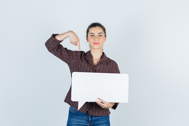 Giovane donna in camicia, jeans rivolti verso il basso, mantenendo un poster di carta e guardando fiducioso, vista frontale.
