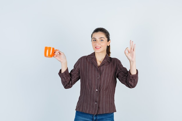 Giovane donna in camicia, jeans che mostrano gesto ok, tenendo la tazza e guardando felice, vista frontale.