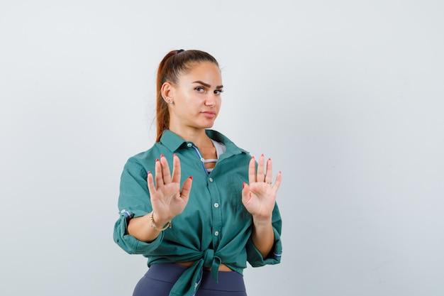 Giovane donna in camicia, pantaloni che mostrano il gesto di arresto e sembrano dispiaciuti, vista frontale.
