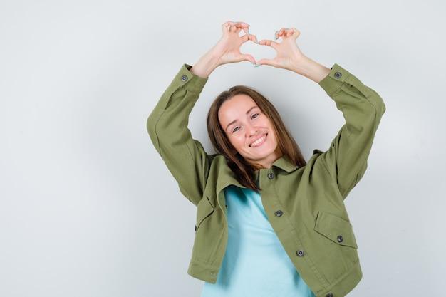 Giovane donna che mostra il gesto del cuore sopra la testa in maglietta, giacca e sembra carina, vista frontale.