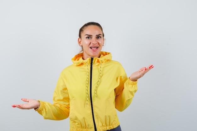 Giovane donna che mostra gesto impotente in giacca gialla e sembra stupita. vista frontale.