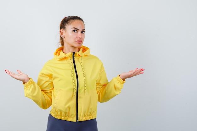 Giovane donna che mostra gesto impotente in giacca gialla e sembra indecisa. vista frontale.
